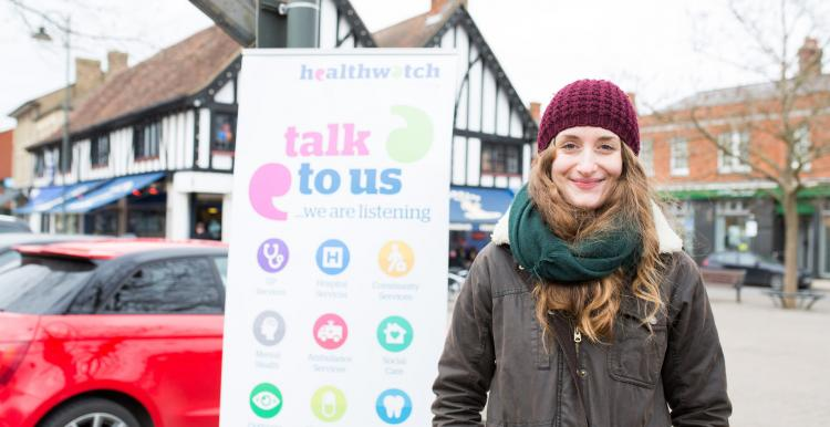 Woman standing outside, in front of a Healthwatch banner
