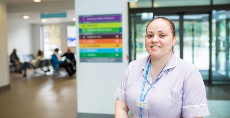 A healthcare assistant standing in the hospital entrance