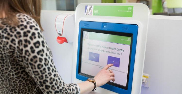 A lady touching an appointment screen in a hospital