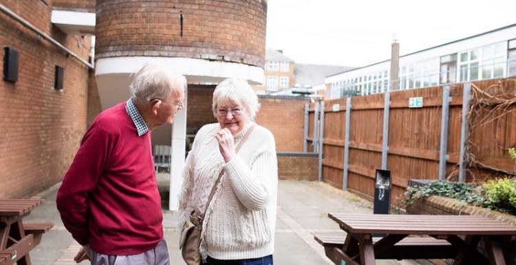 Two elderly people standing outside talking