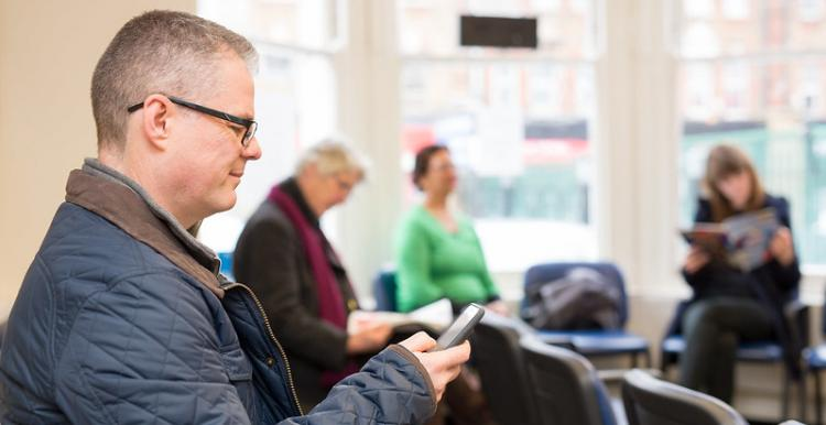 A man in a hospital waiting room looking at his phone