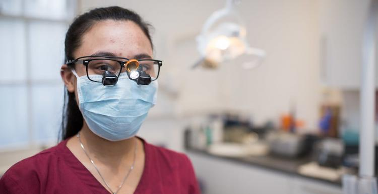 photo of female dentist wearing a mask