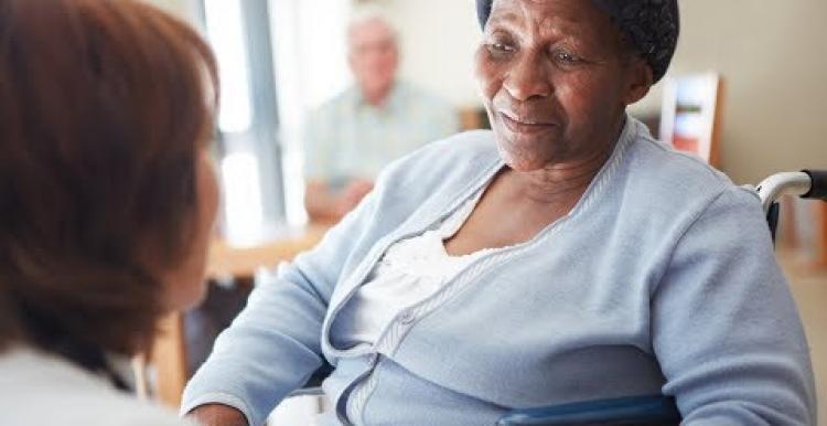 Black elderly woman in a nursing home being spoken to by a nurse