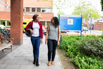 Two females walking outside an accident and emergency department