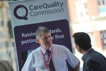 A man standing in front of a CQC sign