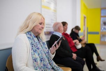 A woman sitting in a waiting room looking at her phone