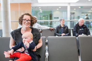 A mother and baby waiting in a waiting room