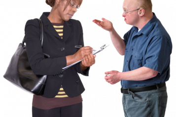 Image of a man making a complaint to a lady who is holding a clip board and writing notes