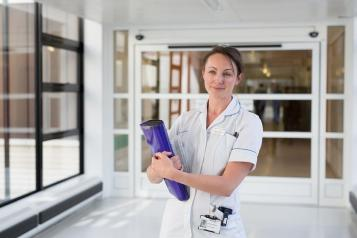 A nurse in a hospital corridor holding a folder and smiling