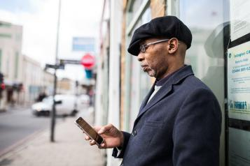 A man standing outside looking at his phone
