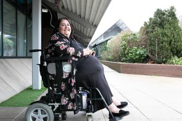 A lady in a wheelchair sitting outside
