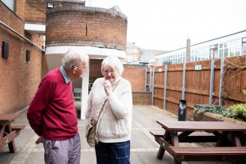 Two elderly people standing outside talking