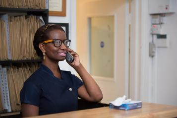 A receptionist on the phone in a hospital