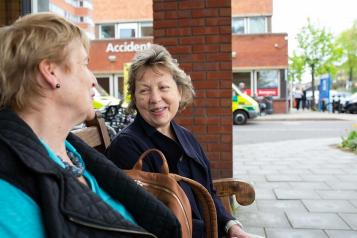 Two ladies sitting outside a hospital on a bench