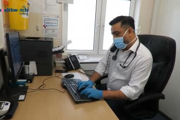 Image of GP at his desk on the phone and typing on his computer simultaneously