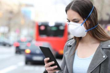 female wearing mask holding phone