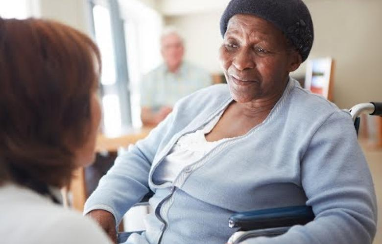 Black elderly woman in a nursing home being spoken to by a nurse