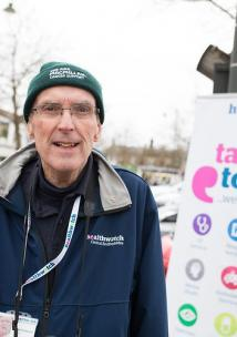A man standing outside in front of a Healthwatch sign